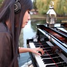 HJ Lim plays piano on a river