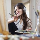 Woman painting listening to music in headphones
